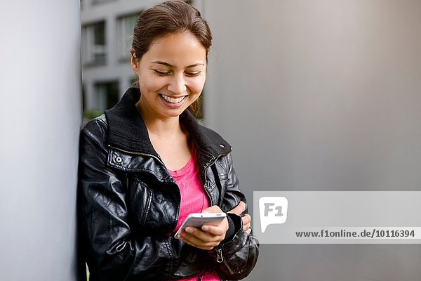 Young woman leaning against pillar reading smartphone texts
