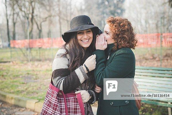 Zwei erwachsene Freundinnen  die im Park flüstern.