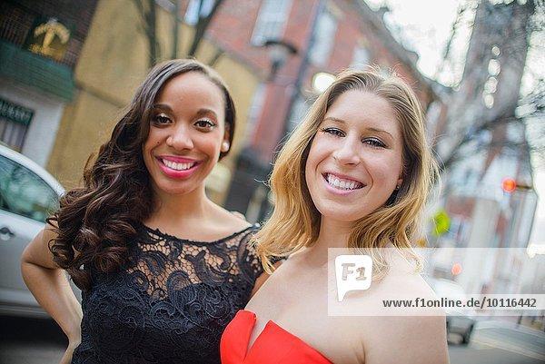 Porträt von zwei glamourösen jungen erwachsenen Freundinnen auf der Straße