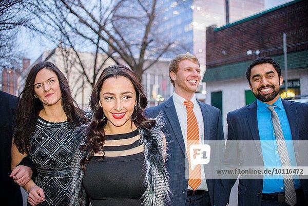 Vier junge erwachsene Freunde bei einem nächtlichen Spaziergang auf der Straße.