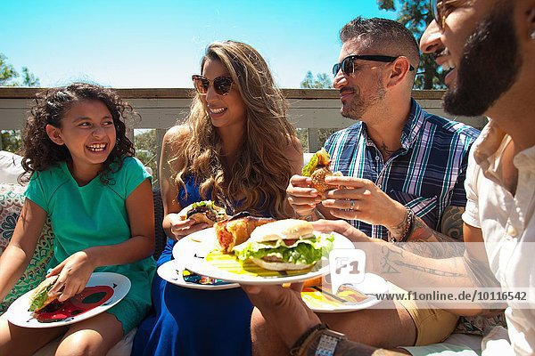 Mid adult family and daughter eating barbecue food in garden
