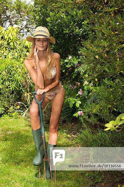 Frau im Bikini im Garten posierend