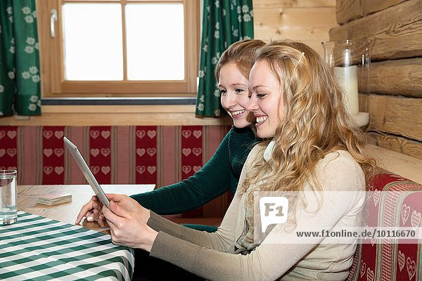 Two young women using digital tablet in log cabin