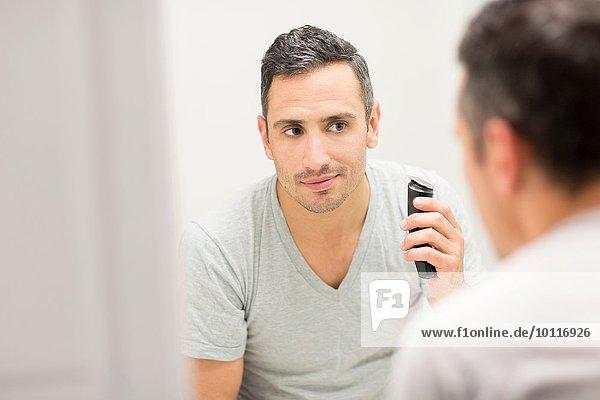 Mittlerer erwachsener Mann  der in den Spiegel schaut und einen elektrischen Rasierer benutzt.