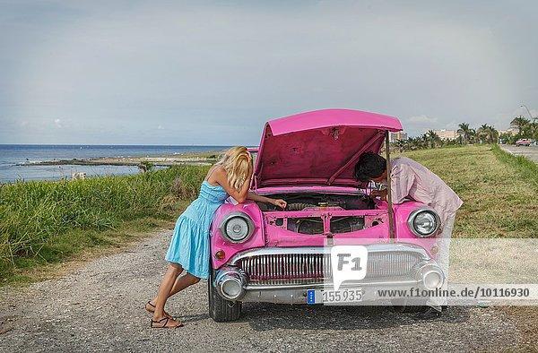 Junges Paar versucht  ein Oldtimer-Cabriolet an der Küste  Havanna  Kuba zu reparieren.