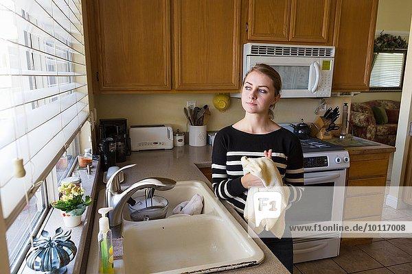 Frau träumt in der Küche