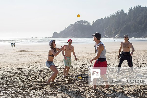 Vier erwachsene Freunde spielen mit Ball am Short Sands Beach  Oregon  USA