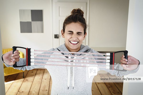 Young woman straining to exercise using chest expander in living room