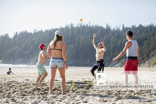 Vier erwachsene Freunde werfen und fangen Ball am Short Sands Beach  Oregon  USA