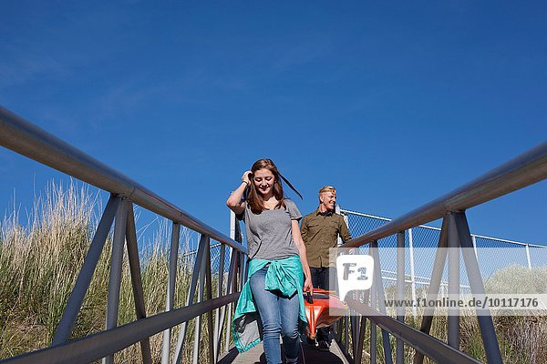Front view of young couple carrying kayak on walkway with railings