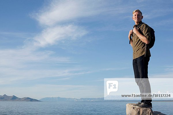 Junger Mann im Rucksack auf dem Felsen stehend  Great Salt Lake  Utah  USA