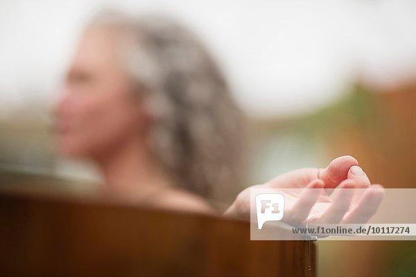 Hand der reifen Frau beim Meditieren im Whirlpool beim Öko-Retreat