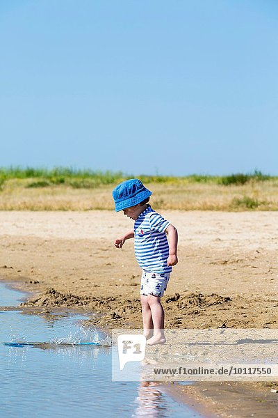 Small boy on beach throwing sand into sea  Marennes  Charente-Maritime  France