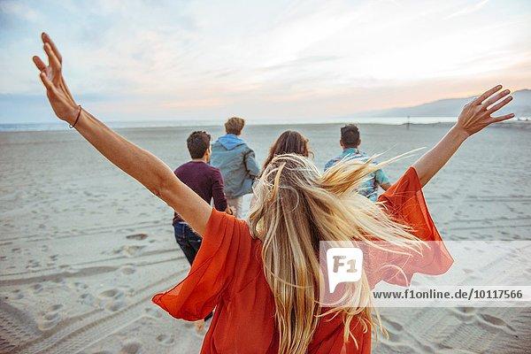 Gruppe von Freunden am Strand entlang  junge Frau mit Armen in der Luft  Rückansicht