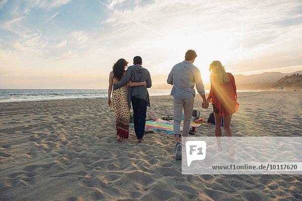Zwei junge Paare gehen am Strand entlang  Rückansicht