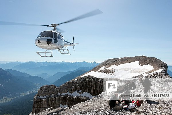 BASE jumpers preparing wingsuits on mountain summit  Dolomites  Italy
