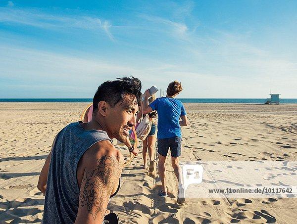 Gruppe von Freunden  die am Strand spazieren gehen  Rückansicht