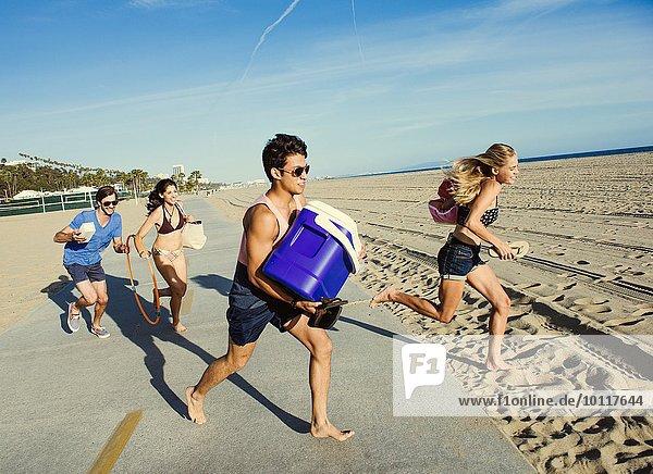 Group of friends  running towards beach