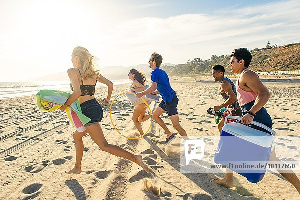 Group of friends running on beach  rear view