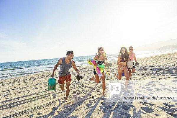 Gruppe von Freunden  die am Strand laufen  lachend