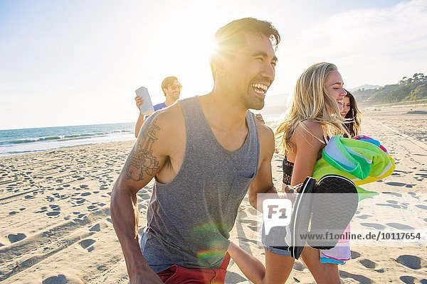 Group of friends walking on beach  laughing