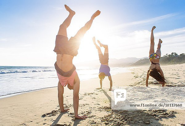 Gruppe von Freunden beim Handstand am Strand