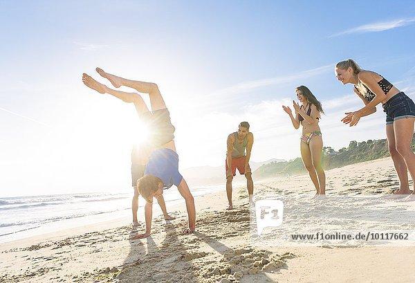 Gruppe von Freunden am Strand beobachten Freund tun Handstand