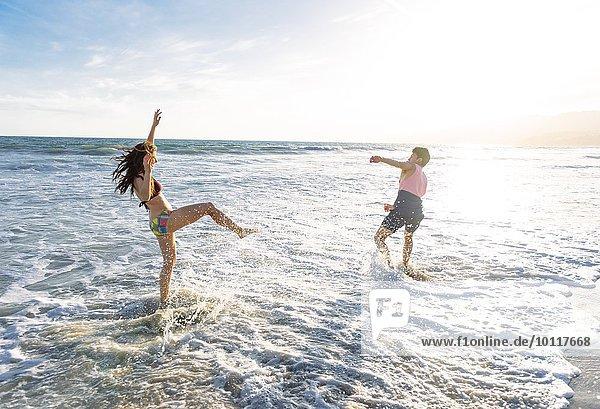 Junges Paar am Strand  das im Meer herumalbert.