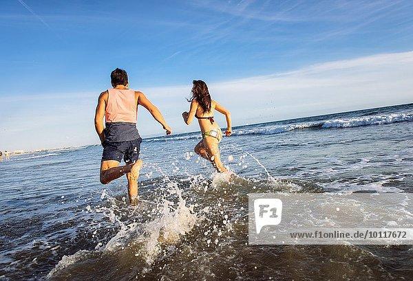 Junges Paar im Meer  Rückansicht