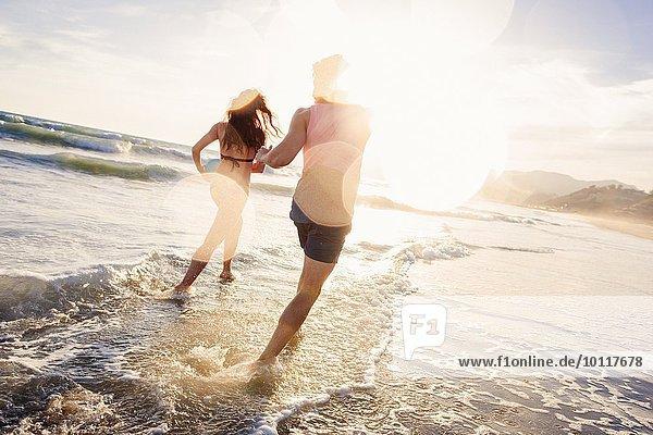 Junges Paar  das im Meer herumalbert.