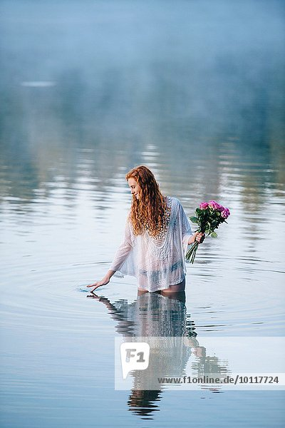 Young woman standing in lake holding bunch of roses and rippling surface with her fingers