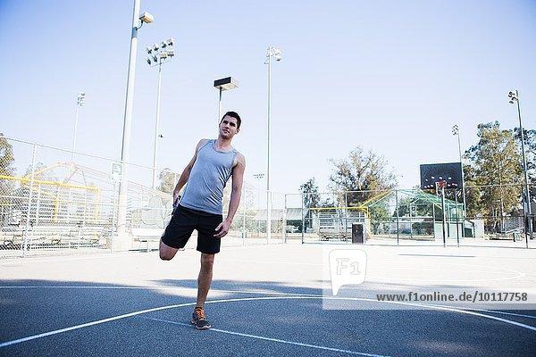 Junger Basketballspieler beim Aufwärmen auf dem Basketballplatz