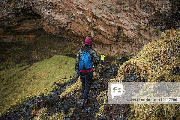 Zwei Touristen wandern am Seljalandsfoss Wasserfall  Island