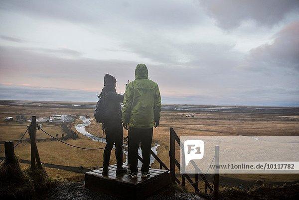 Männliche und weibliche Touristen fotografieren von der Aussichtsplattform am Seljalandsfoss  Island