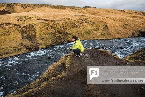 Männliche Touristen hocken am Flussufer  Skogafoss  Island