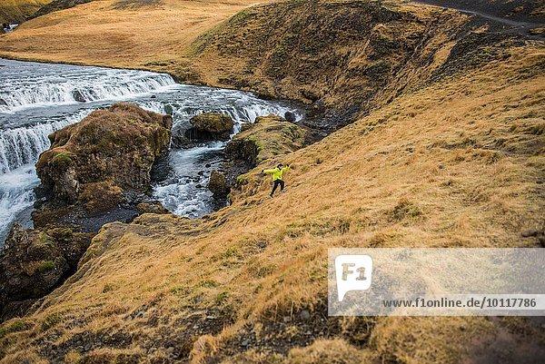 Männlicher Tourist  der in Skogafoss  Island  den Berg hinaufläuft.