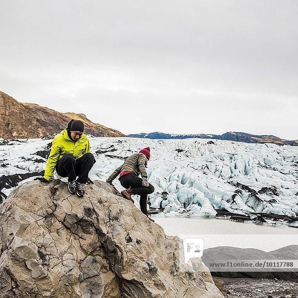 Männliche und weibliche Touristen klettern auf Felsbrocken bei Solheimajokull  Island