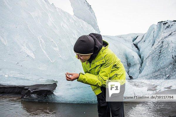 Männlicher Tourist beim Betrachten des Eisfragments in Solheimajokull  Island