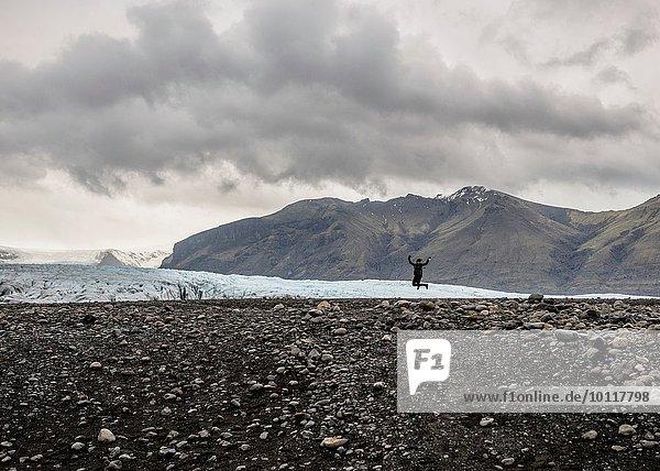 Silhouette der weiblichen Touristen  die vor dem Gletscher springen  Skaftafell  Island