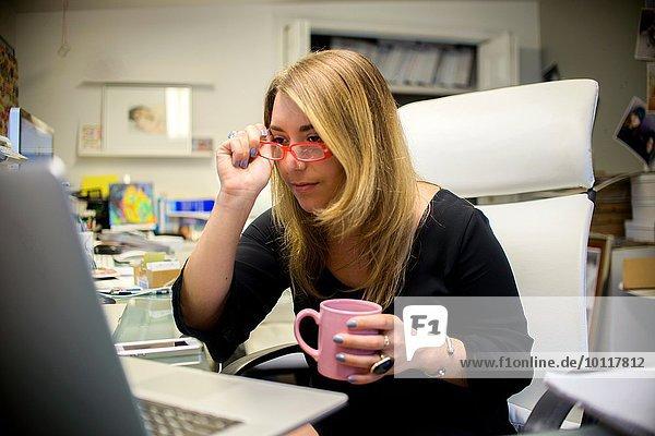 Junge Frau im Büro  am Schreibtisch sitzen  Kaffeetasse halten  Gläser aufsetzen