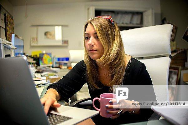 Junge Frau im Büro  am Schreibtisch sitzend  Kaffeetasse haltend  mit Laptop