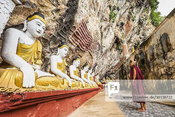 Monk looking at the seated Buddha statues  Kawgun Cave  Hpa-an  Karen or Kayin State  Myanmar  Asia