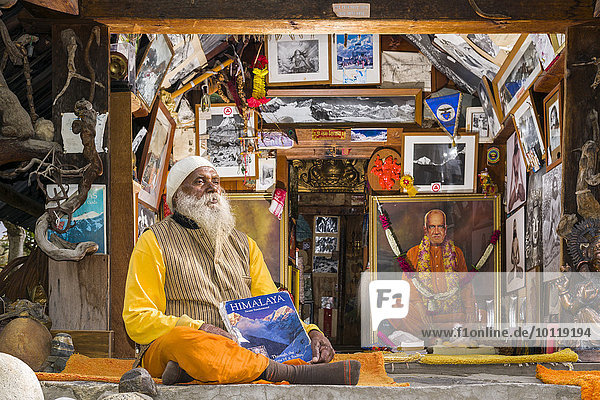 Swami Sundaranand  ein berühmter Sadhu  Yogi und Fotograf  sitzt vor seinem Haus mit seinem Buch  Gangotri  Uttarakhand  Indien  Asien