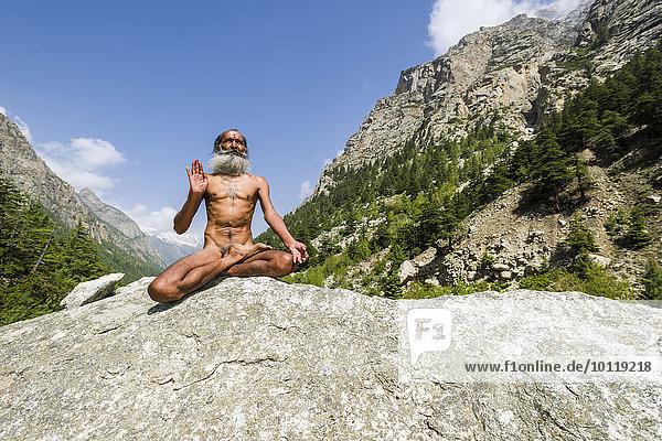 Mahant Naomi Giri  52 Jahre  Sadhu  im Lotussitz  padmasana  auf einem Felsen am Ufer des heiligen Flusses Ganges  Gangotri  Uttarakhand  Indien  Asien