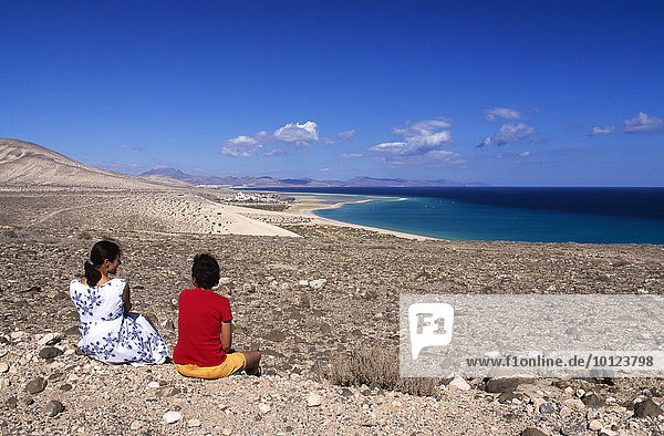 Zwei Frauen sitzen mit Blick auf Küste bei den Playas de Sotavento  Fuerteventura  Kanarische Inseln  Spanien  Europa