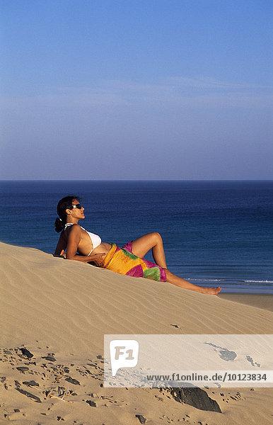 Frau liegt auf Sanddüne bei den Playas de Sotavento  Fuerteventura  Kanarische Inseln  Spanien  Europa