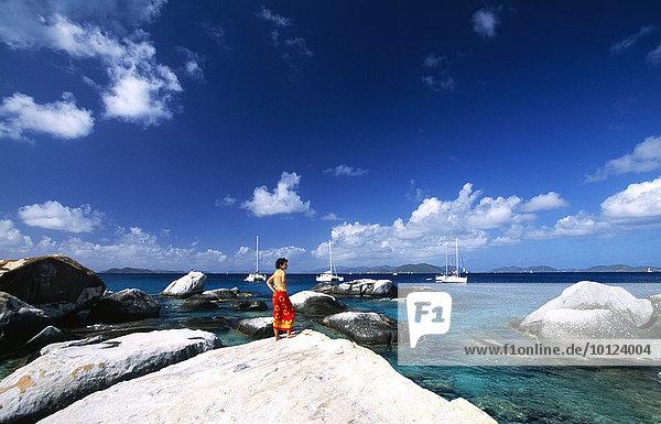 Frau betrachtet Felsformation The Baths auf der Insel Virgin Gorda  Britische Jungferninseln  Karibik  Nordamerika
