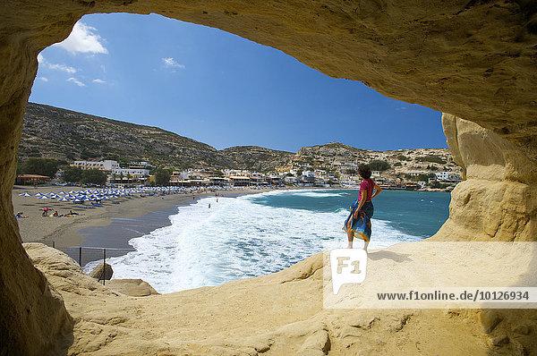 Frau steht vor Höhle am Strand von Matala  Kreta  Griechenland  Europa