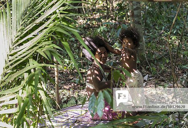 Frau der Orang Asil sitzt mit ihrem Kind unter Palmwedeln im Dschungel  Ureinwohner  tropischer Regenwald  indigenes Volk  Nationalpark Taman Negara  Malaysia  Asien