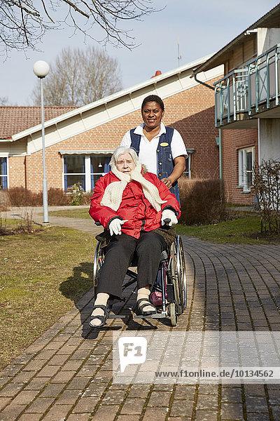 Senior Senioren Frau gehen Rollstuhl
